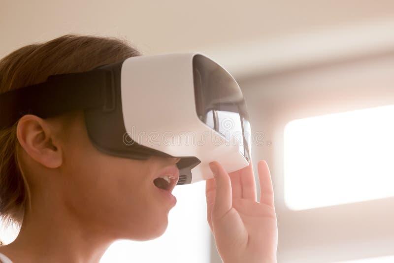 Kvinna i VR-hörlurar med mikrofon som förvånas av virtuell verklighet arkivbild