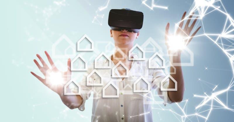 Kvinna i VR med vita husdiagram mot blå bakgrund med signalljus royaltyfri fotografi