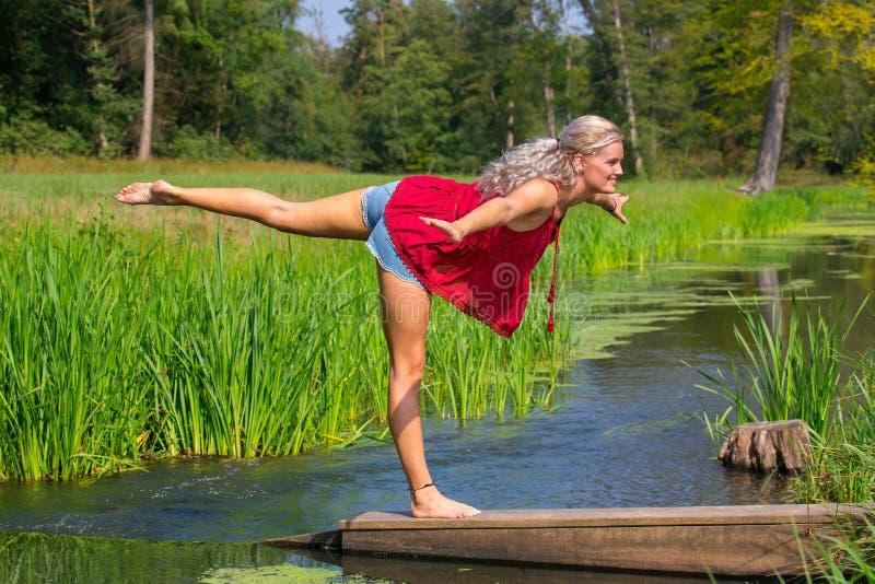 Kvinna i yogaställing på ett ben i natur arkivfoto
