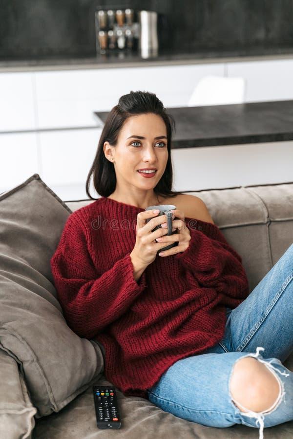 Kvinna inomhus i hem på soffaklockaTV som dricker kaffe royaltyfria foton