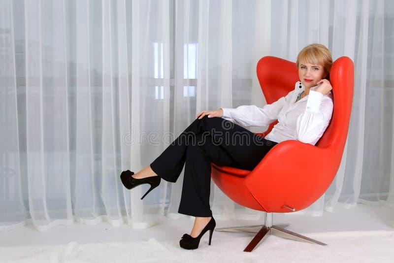 Kvinna ledare, som sitter i en röd stol royaltyfri fotografi