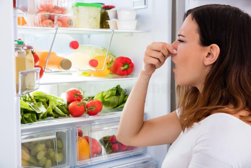 Kvinna märkt lukt i Front Of Refrigerator arkivbilder
