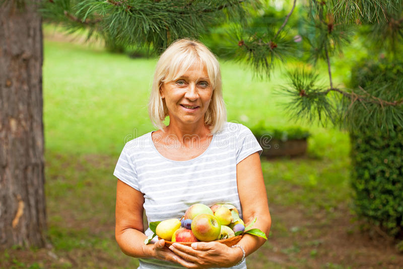 Kvinna med äpplen och päron arkivfoto