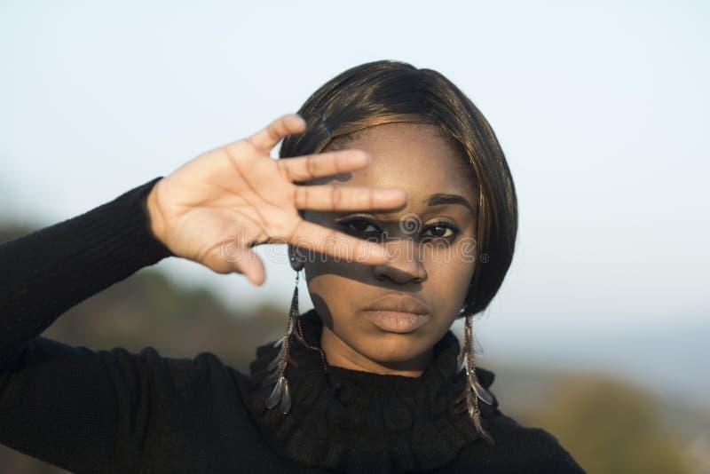 Kvinna med afrikanskt utseende mot solljus, ljus bakgrund som ?r defocused Flicka p? den lugna avkopplade framsidan som d?ljer ut royaltyfria foton