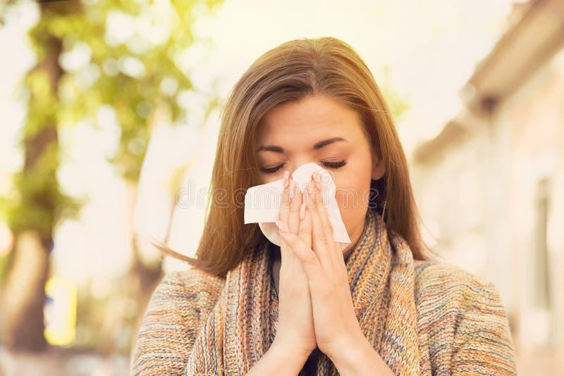 Kvinna med allergitecken som blåser näsan royaltyfri fotografi