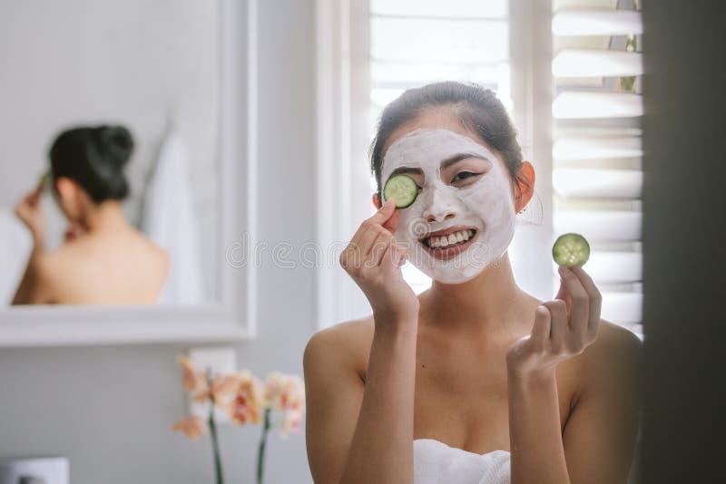 Kvinna med ansiktsmask i badrum royaltyfri fotografi