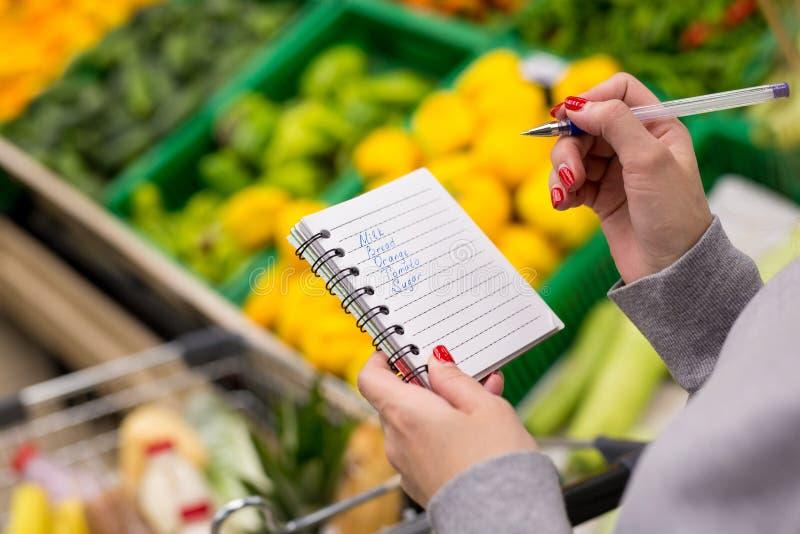 Kvinna med anteckningsboken i livsmedelsbutiken, closeup Shoppinglista på papper royaltyfria bilder