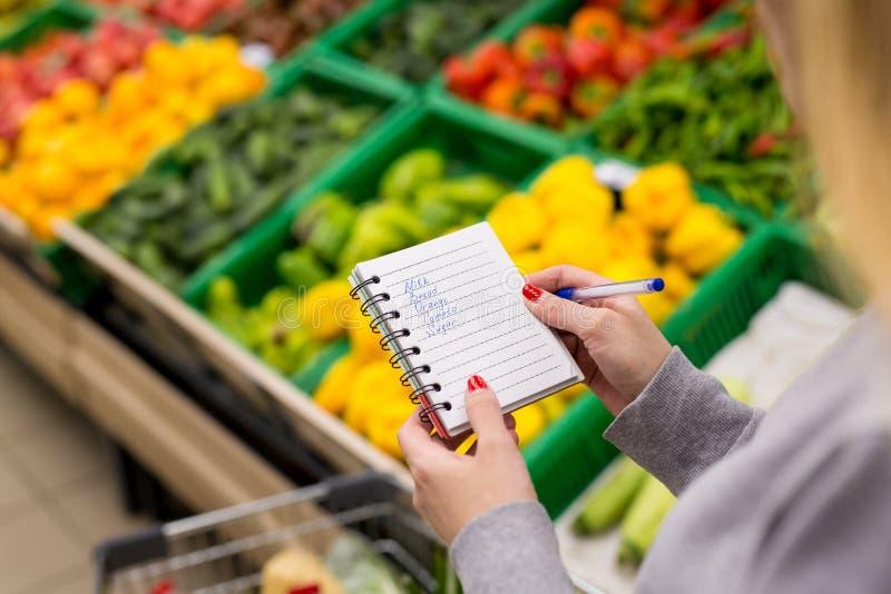 Kvinna med anteckningsboken i livsmedelsbutiken, closeup Shoppinglista på papper arkivfoto