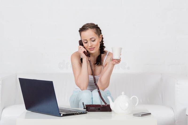 Kvinna med anteckningsboken och telefonen. arkivfoto
