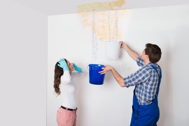Kvinna med arbetaren som samlar vatten från tak i hink arkivfoto