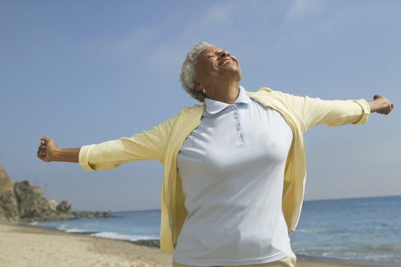 Kvinna med armar som är utsträckta på stranden fotografering för bildbyråer