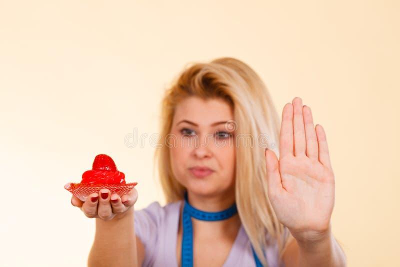 Kvinna med att mäta för muffinvisning för band det hållande stoppet royaltyfria foton