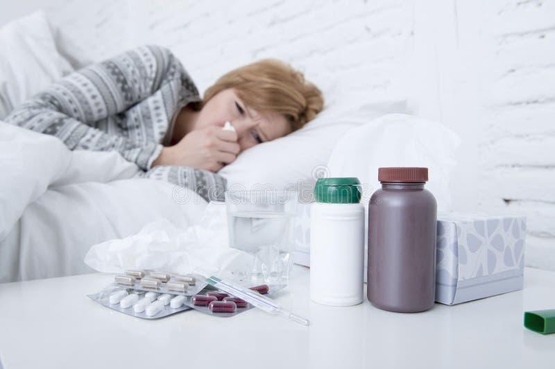 kvinna med att nysa näsan som blåser i silkespapper på tecken för virus för influensa för sänglidande som kalla har medicinminnes arkivbilder
