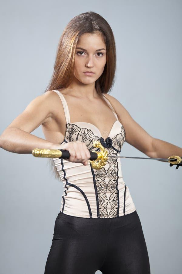 Kvinna med att posera för svärd royaltyfri foto