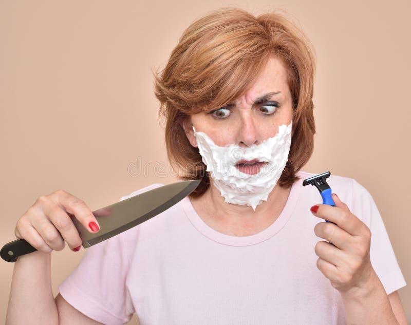 Kvinna med att raka skum på hennes framsida som rymmer en kniv och en rakkniv royaltyfri foto