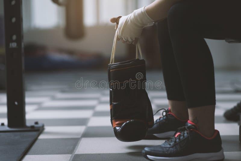 Kvinna med att stansa handskar som vilar på en bänk royaltyfri bild