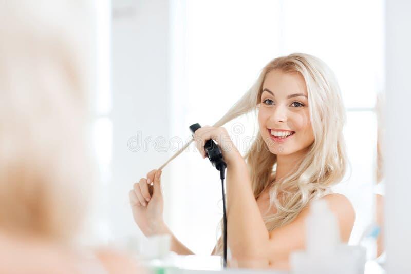 Kvinna med att utforma järn som gör hennes hår på badrummet fotografering för bildbyråer
