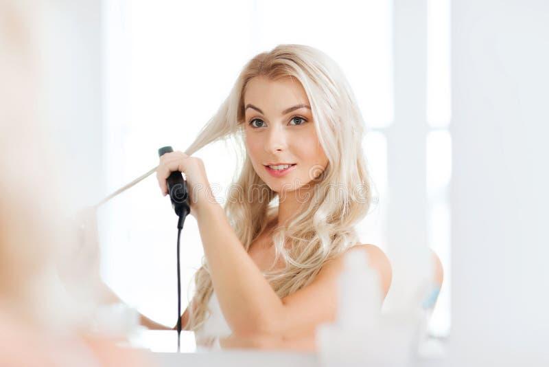 Kvinna med att utforma järn som gör hennes hår på badrummet arkivbilder