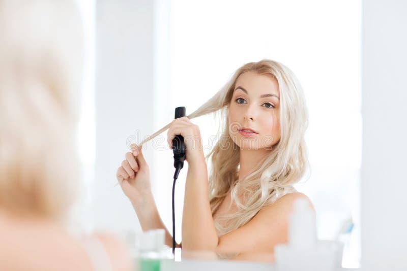 Kvinna med att utforma järn som gör hennes hår på badrummet royaltyfria foton