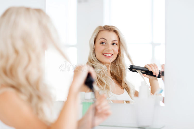 Kvinna med att utforma järn som gör hennes hår på badrummet royaltyfri bild