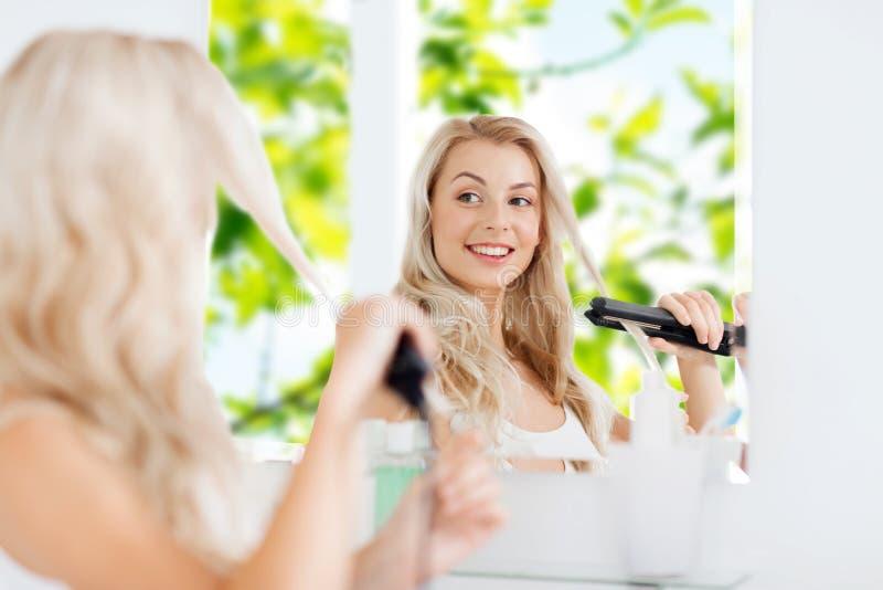 Kvinna med att utforma järn som gör hennes hår på badrummet royaltyfri fotografi