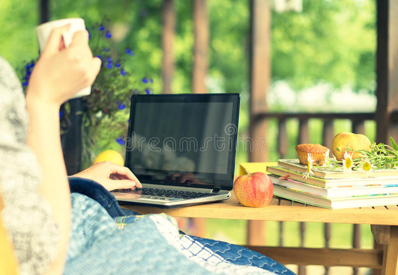 Kvinna med bärbar dator och koppen royaltyfri fotografi