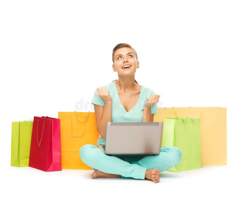 Kvinna med bärbar dator- och shoppingpåsar royaltyfri bild