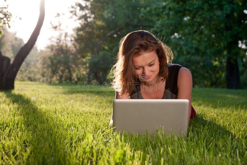 Kvinna med bärbar dator på gräset royaltyfri bild