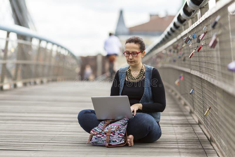 Kvinna med bärbar datorsammanträde på en fot- bro i en gammal europeisk stad royaltyfri bild