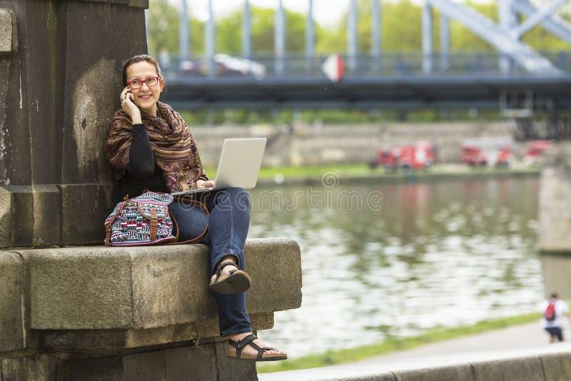 Kvinna med bärbar datorsammanträde som talar utomhus på telefonen Lyckligt arkivfoton