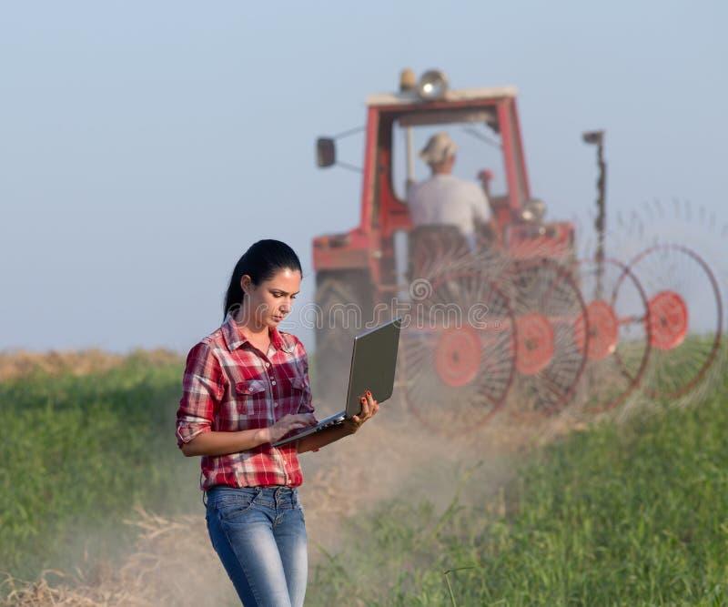 Kvinna med bärbara datorn i fältet arkivbilder