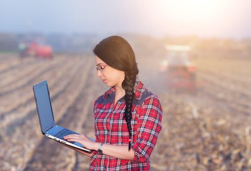 Kvinna med bärbara datorn i havrefält royaltyfri fotografi