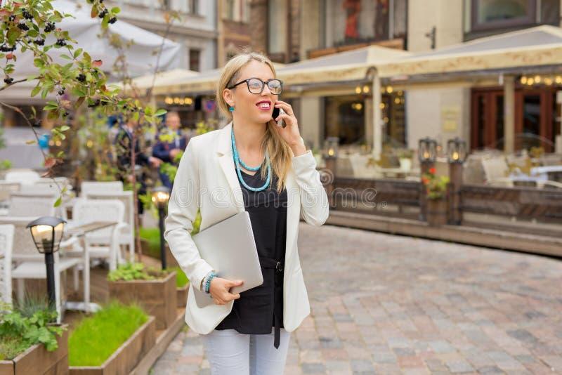 Kvinna med bärbara datorn i hennes hand som talar på telefonen fotografering för bildbyråer