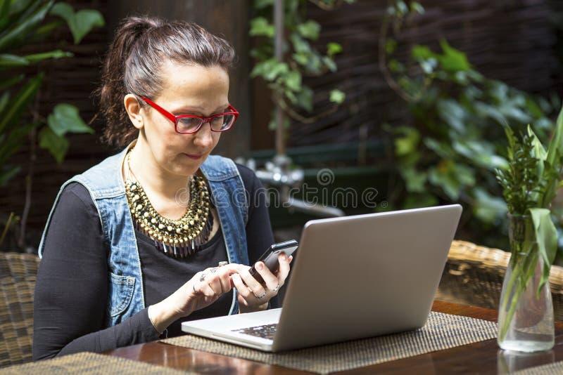 Kvinna med bärbara datorn och smartphonen i sommarkafé Student fotografering för bildbyråer