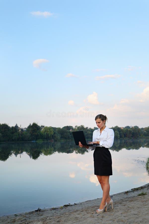 Kvinna med bärbara datorn på kusten arkivbilder