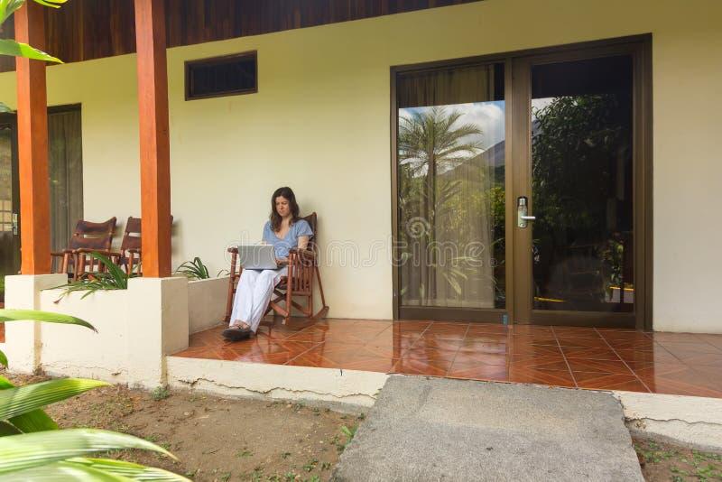 Kvinna med bärbara datorn på verandan arkivfoto