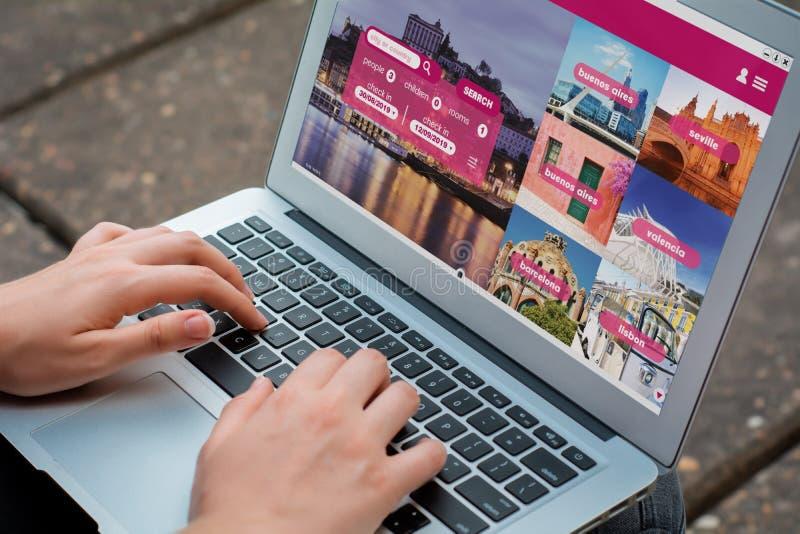 Kvinna med bärbara datorn som bokar ett hotell på websiten royaltyfri foto