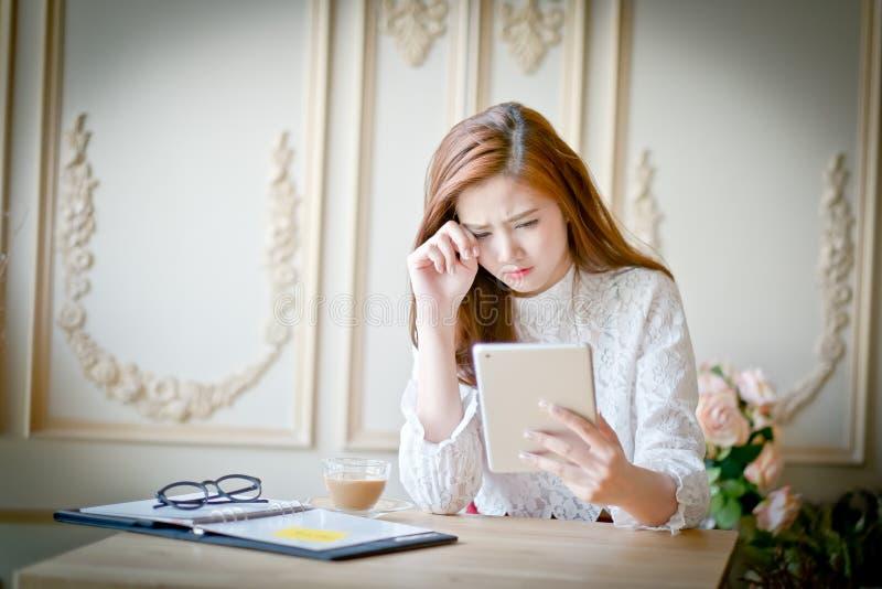 Kvinna med bärbara datorn som håller ögonen på ledsen film arkivfoto
