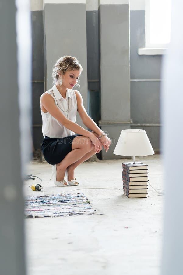 Kvinna med böcker och den ljusa ljusa kulan royaltyfri foto