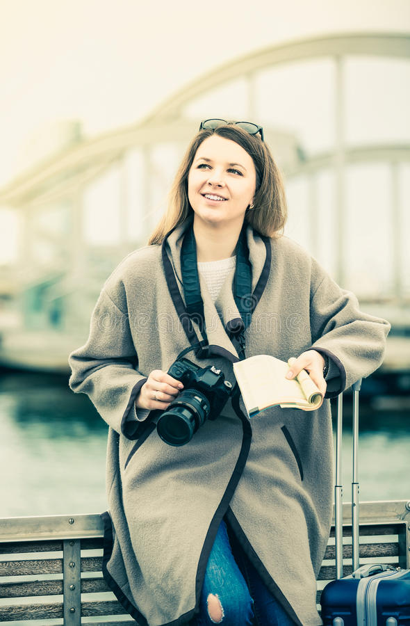 Kvinna med bagage som poserar på kajen och att le royaltyfri fotografi
