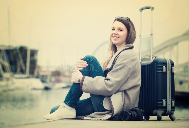 Kvinna med bagage som poserar på kajen och att le royaltyfria foton