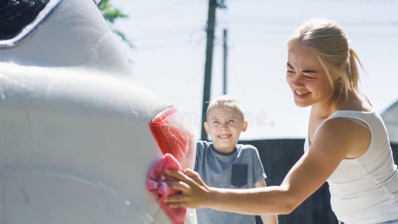 Kvinna med barn som tvättar bilen arkivbild