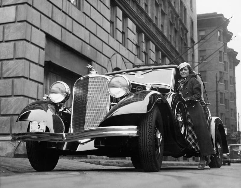 Kvinna med bilen på stadsgatan (alla visade personer inte är längre uppehälle, och inget gods finns Leverantörgarantier som där w fotografering för bildbyråer