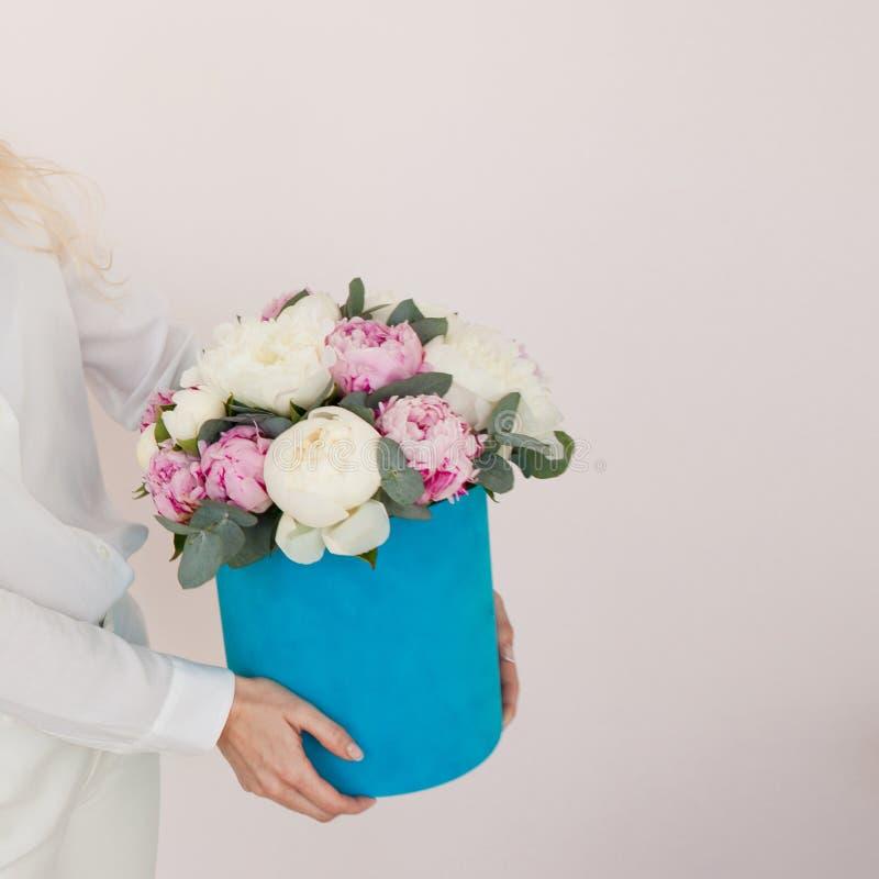 Kvinna med blommor i en hattask Bukett av pioner Kvinnors händer som rymmer en gåvaask med blommor royaltyfri fotografi