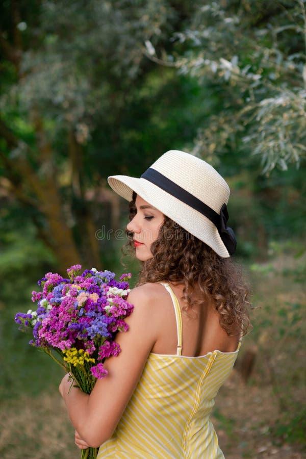 Kvinna med blommor i händer, bärande vit hatt royaltyfria bilder