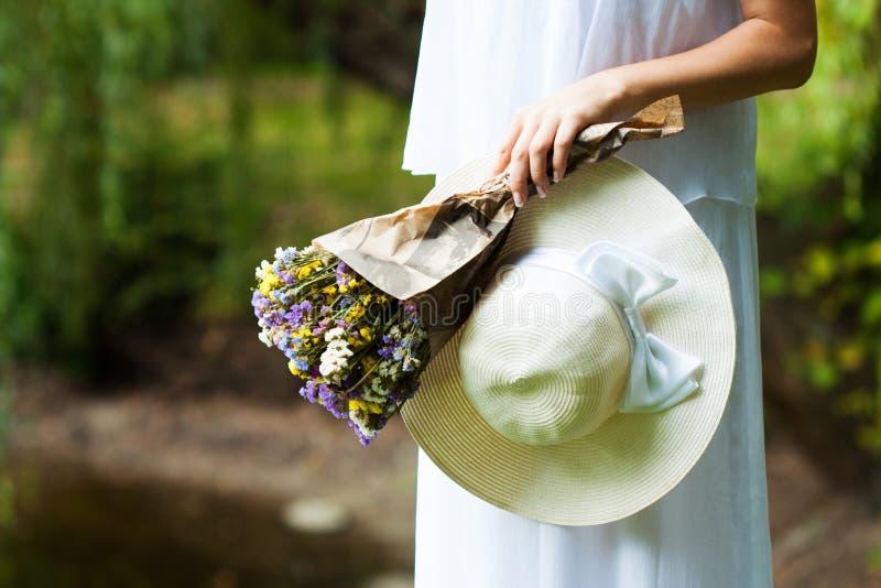 Kvinna med blommor och hatten i händer Närbild arkivbild