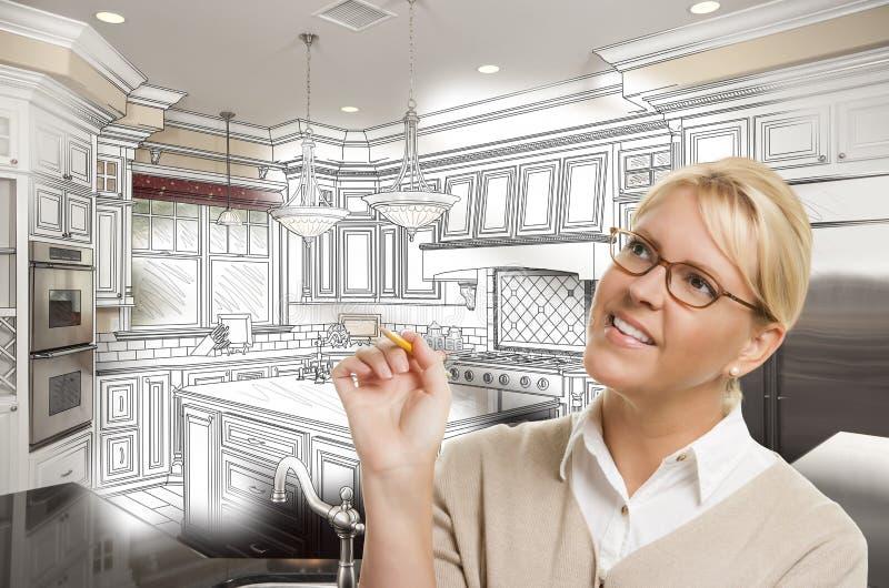 Kvinna med blyertspennan över beställnings- kökdesignteckning och foto C arkivbild