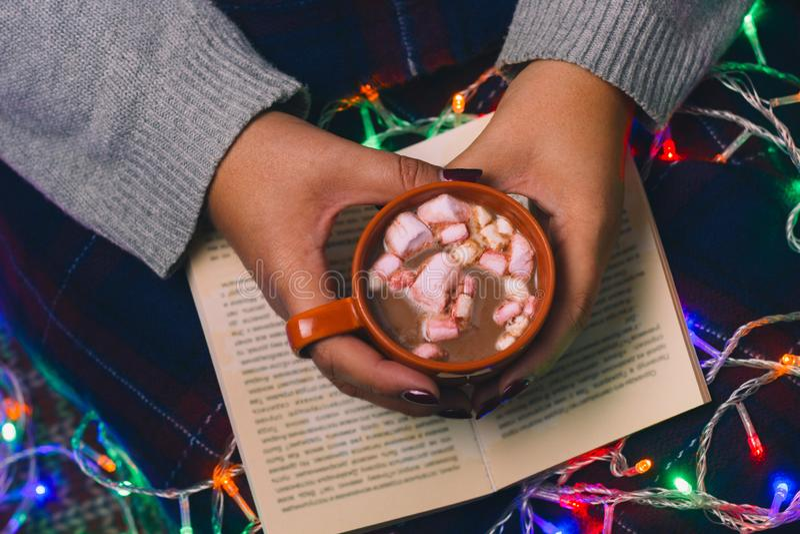 Kvinna med bok och varm drink I royaltyfri fotografi