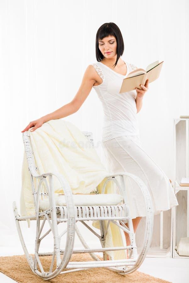 Kvinna med boken i vardagsrum royaltyfria foton