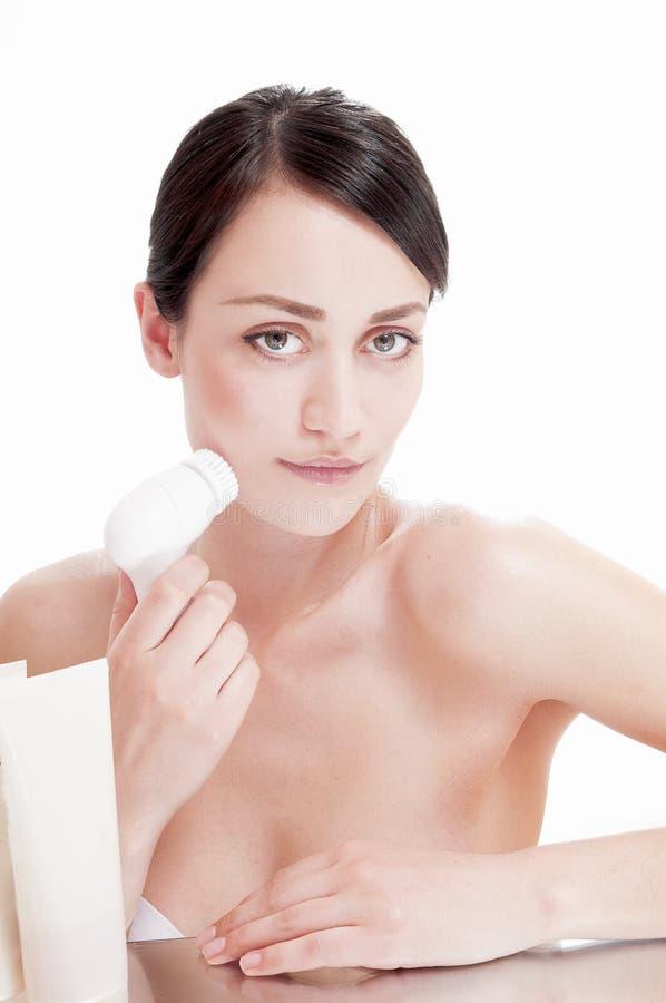 Kvinna med borsten för djup rentvå ansiktsbehandling. arkivfoton